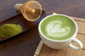Matcha latte art heart shape on top on wooden table with some green tea powder beside and tools for tea making, Japanese style