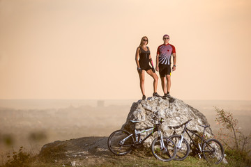 Summer evening. Cyclists standing on a large stone on the precipice of a cliff next to them are sports bikes. Blurred background with copy space