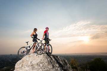 Athletes with mountain bikes standing on the rock under the evening sky and looking into the distance at the sunset