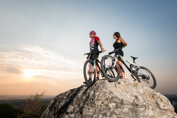 Couple cyclist, man and woman, with mountain bikes standing on the rock under the evening sky and looking into the distance at the sunset