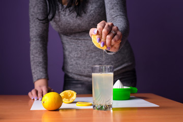 Girl is squeezing lemon with her hand