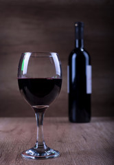Glass of wine with a bottle on a wooden backgound