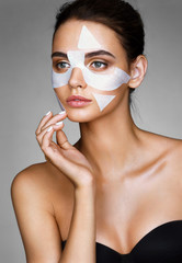 Beautiful woman with cotton facial mask. Photo of brunette woman on grey background. Skin care concept