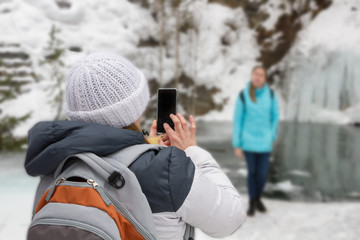 photo on the phone on a journey in the winter. Girl in a hat in a jacket with a backpack Woman photographed blur background water rock ice, missed first trimester waterfall.