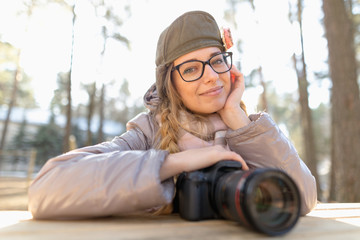 girl in sunglasses with a camera in nature.