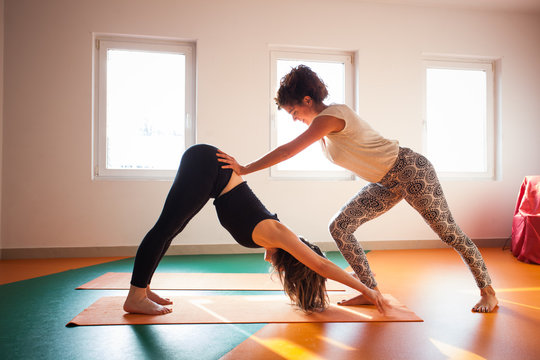 yoga instructor assisting student in exercis