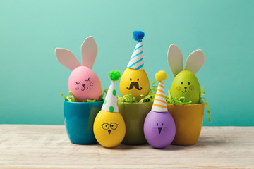 Easter holiday concept with cute handmade eggs in coffee cups, bunny, chicks and party hats