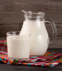 jug and glass of milk on a wooden background