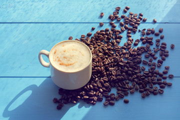 spring sunny coffee/ cup of frothy cappuccino flavored with cinnamon standing on a blue table in a pile of coffee beans