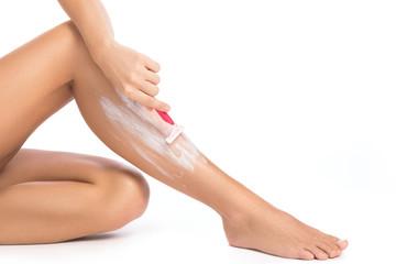 Female legs and shaving razor