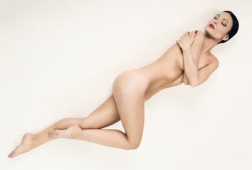 Young naked woman standing on white background
