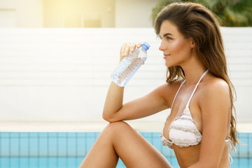 Woman with a bottle of water beside a swimming pool