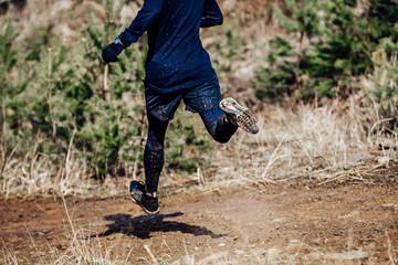 Wall Mural - foot male runner runs dirty trail from mountain