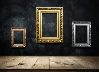Antique picture Frame copper, silver, gold on dark grunge wall with Wooden table top, Empty ready for product display or montage.