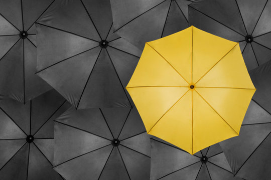 Unique yellow umbrella among many dark ones. Standing out from crowd, individuality and difference concept.