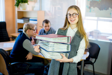 girl holding a stack of documents