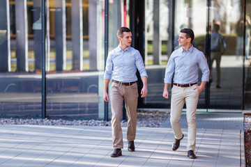 Two businessman walking and talking about business with street city blur background
