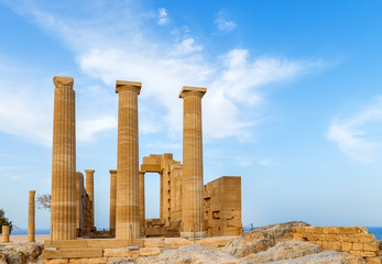 Ancient Greek pillars at Lindos acropolis with blue cloudy sky in the background