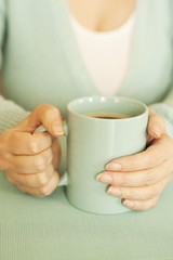 a woman with aquamarine mug filled with coffee over geen blue bacground with copy space
