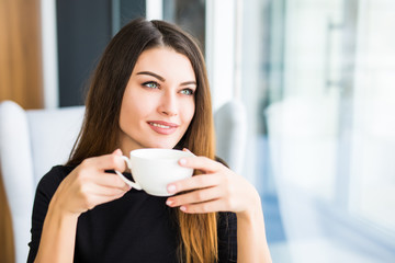 beautiful young woman drinking coffee look in window