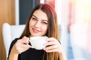 beautiful young woman drinking coffee or tea and look at camera