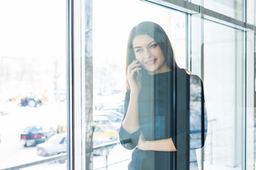 View though the window of successful businesswoman talking on mobile phone with her partners while sitting in cafe during work break.