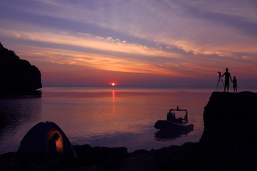 Family camping on the island with private boat and purple sky sunset background.