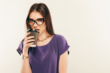 young beautiful girl in glasses with cup of coffee from a fast food on a gray background