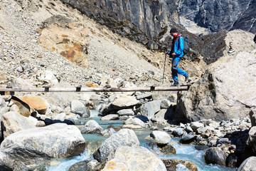 Hiker crossing Mountain River throw wooden Bridge