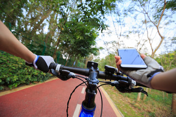 cyclist hands use gps navigator on smartphone while biking
