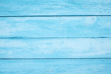 Horizontal planks of wood, painted by light blue color.