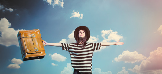 beautiful young woman with brown suitcase standing on the wonderful sky background