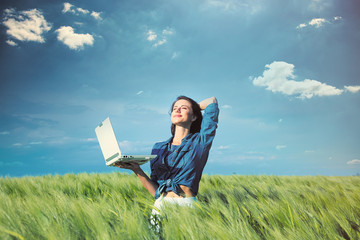 beautiful young woman with laptop standing in the middle of the wonderful green field