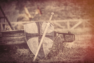cool metallic sword and heavy shield on the middle ages wagon background