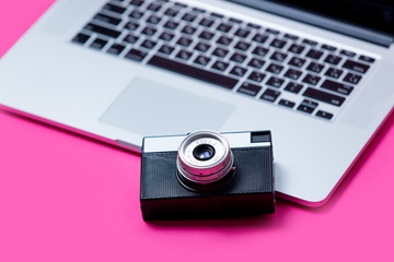 beautiful black camera and cool laptop on the wonderful pink background