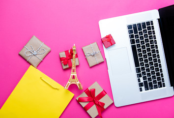 beautiful eiffel tower shaped toy, cute gifts, shopping bag and cool laptop on wonderful pink background