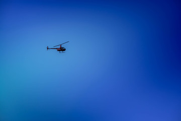 Military helicopter flying in the sky over a city and crowded event, taking photos, filming from above on clear blue sky background. An Isolated helicopter. Team of rescuers searching for lost people