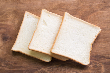 Sliced bread on wooden background.