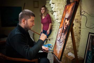 Young artist in studio painting portrait