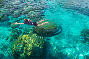 Young man snorkeling over coral reef in transparent tropical sea, Rok island, Thailand.