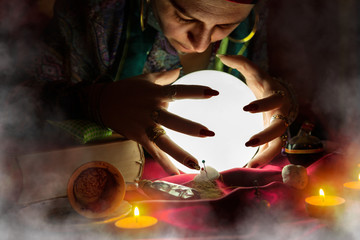 Gypsy woman fortune teller looking at crystal ball