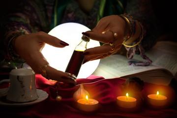 Bottle of love potion in hands of fortune teller