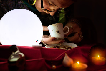 Fortune teller looking and read a fortune from coffee mug
