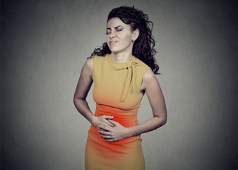 Young woman with hands on stomach having bad aches pain