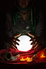 Hands from gypsy fortune teller above magic crystal ball