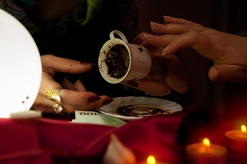 Gypsy fortune teller holds a coffee cup for fortune telling