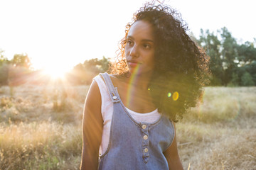 portrait outdoors of a young afro american woman. Yellow background. Lifestyle