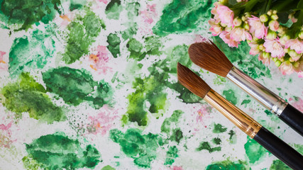 Abstract art hand watercolor and brushes, floral background. Romantic concept of spring, lifestyle, hobbies. Top view. With place for your text, for backdrop, substrate, composition use.