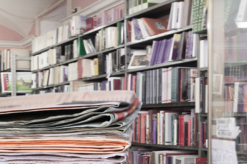Newspapers stacked on book store, library background. Copy space.