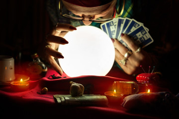 Gypsy woman looking at crystal ball and holding a tarot cards